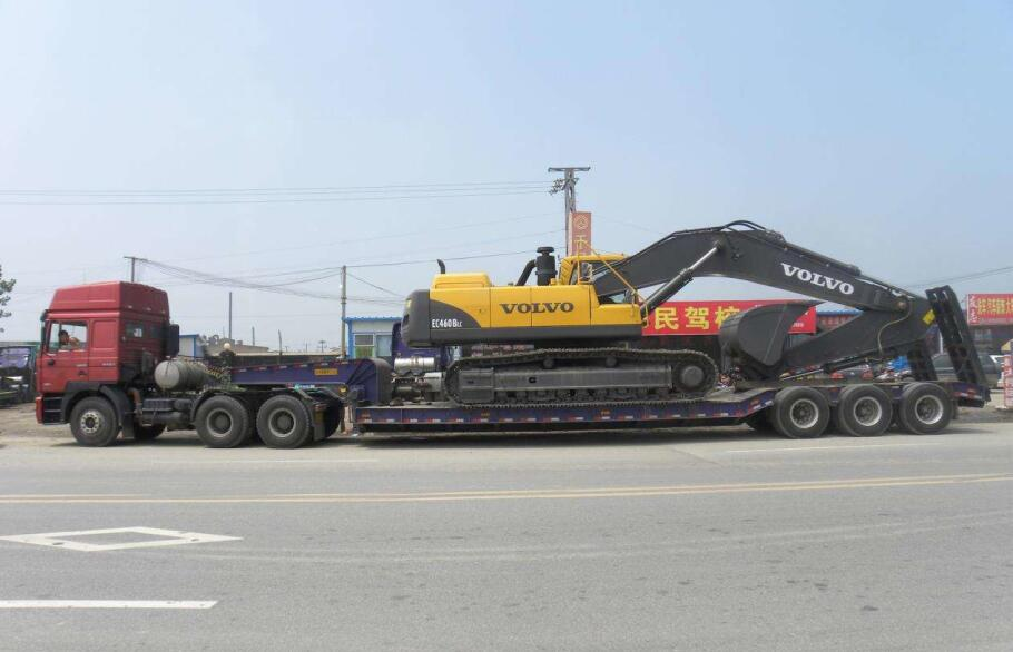 Excavator by low loader trailer